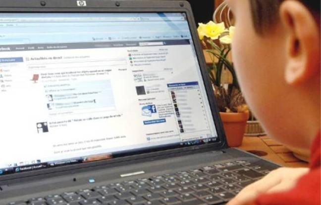 Un adolescent se connecte sur Facebook.