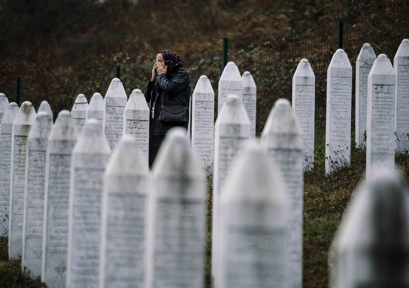 A Bosnian woman offers prayers beside gravestone at the memorial center of Potocari near Srebrenica on November 21, 2017.  On November 22, 2017, ICTY judges will deliver their verdict on Bosnian Serb wartime military chief Ratko Mladic, who faces 11 charges including genocide, war crimes and crimes against humanity -- arising from Bosnia's 1992-1995 war.