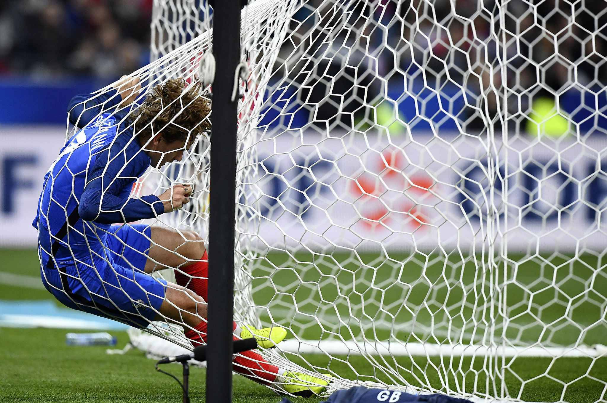 France's forward Antoine Griezmann falls into the net of the goal during the friendly football match France vs Spain on March 28, 2017 at the Stade de France stadium in Saint-Denis, north of Paris. Spain won the match 0-2.