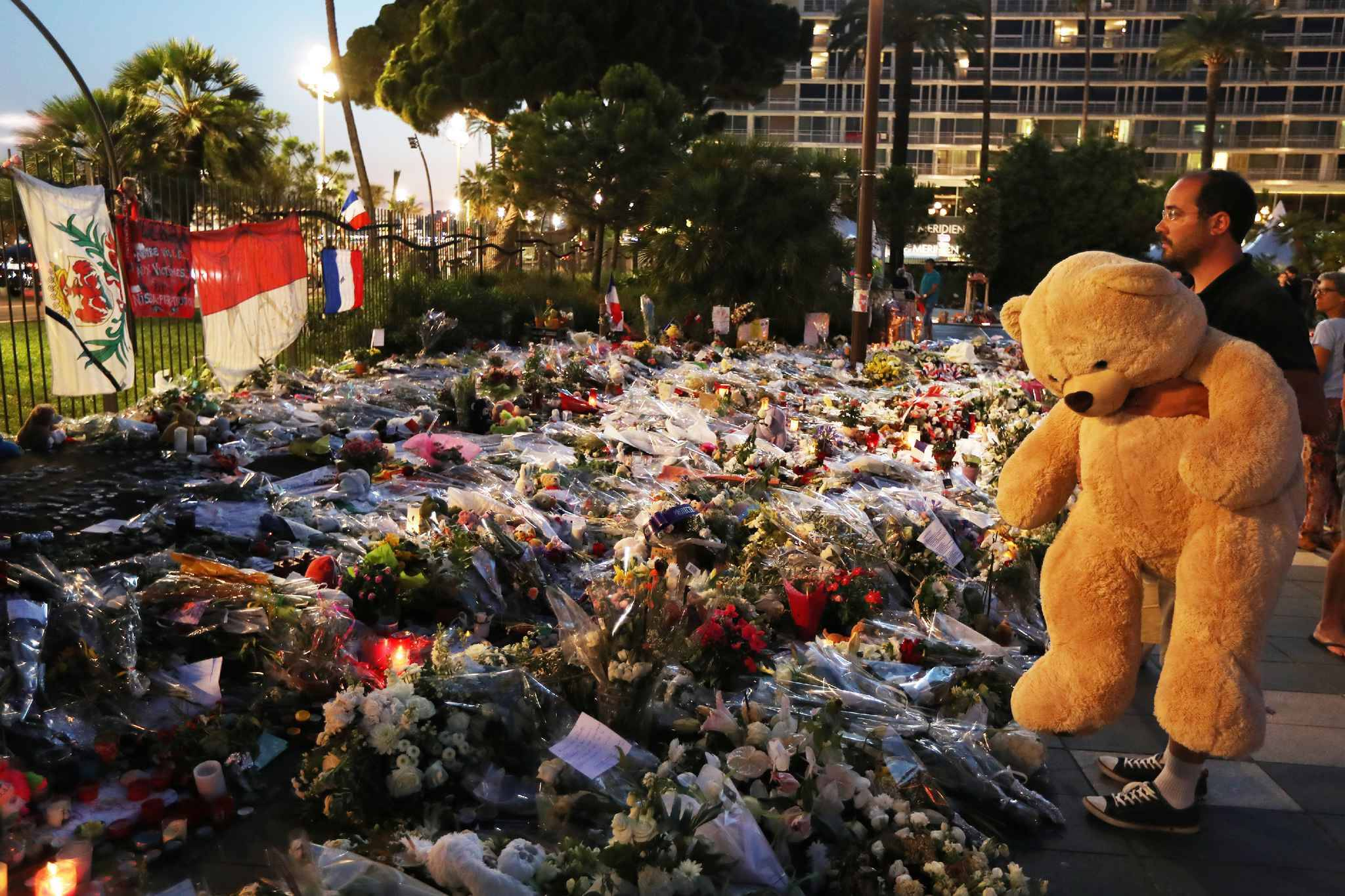 A man holds a giant teddy bear in front of a makeshift memorial near the Promenade des Anglais in Nice on July 19, 2016 in tribute to the victims of the Bastille Day attack.  President Francois Hollande said on July 19 he was willing to extend France's state of emergency for another six months following the Bastille Day massacre, as lawmakers prepared to debate the country's tough security laws. / AFP PHOTO / VALERY HACHE