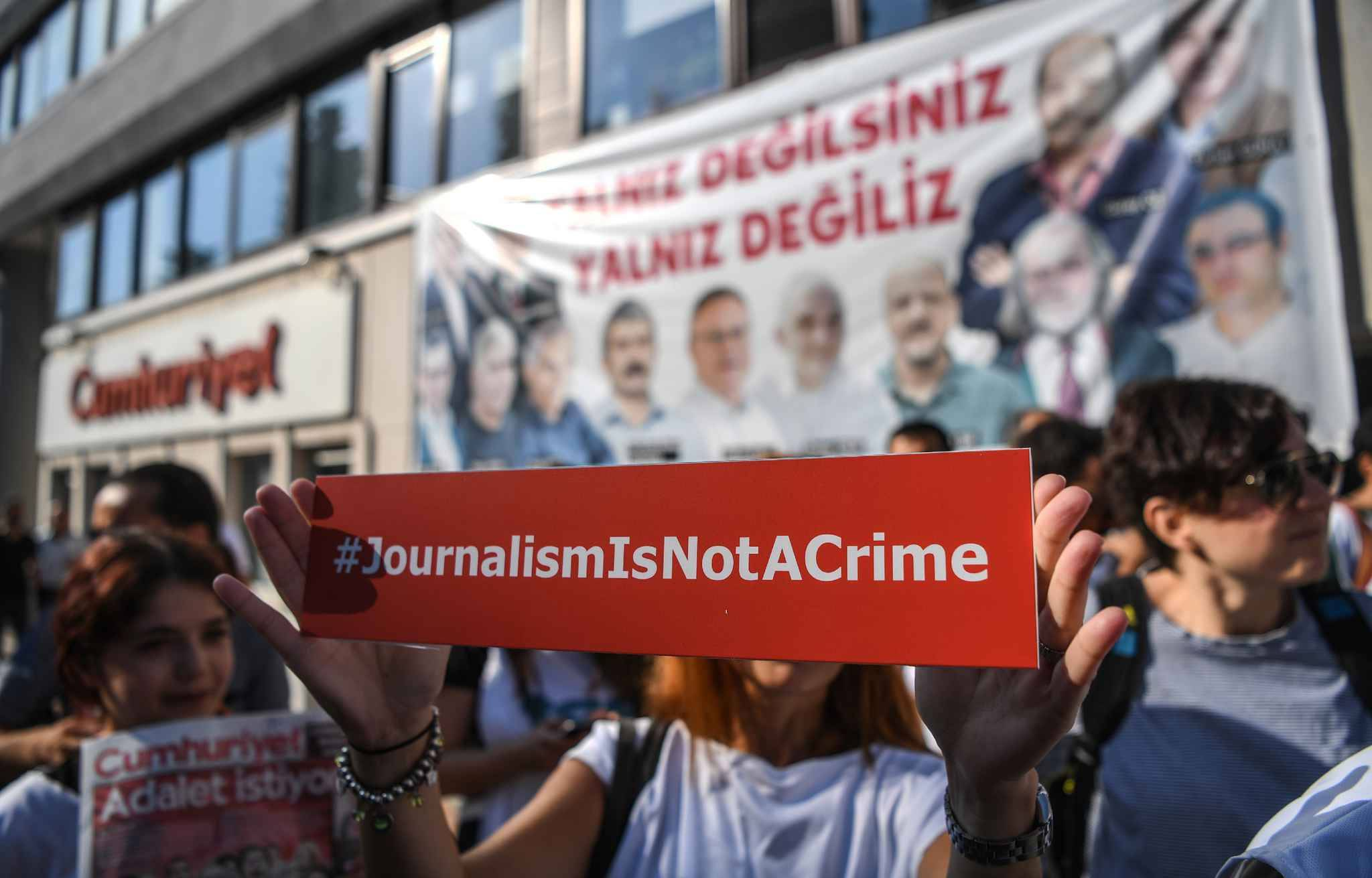 A journalist holds a banner on July 24, 2017 outside the headquarters of opposition daily newspaper Cumhuriyet in Istanbul.  Seventeen directors and journalists from one of Turkey's most respected opposition newspapers go on trial on July 24 after spending over eight months behind bars in a case which has raised new alarm over press freedoms under President Recep Tayyip Erdogan.