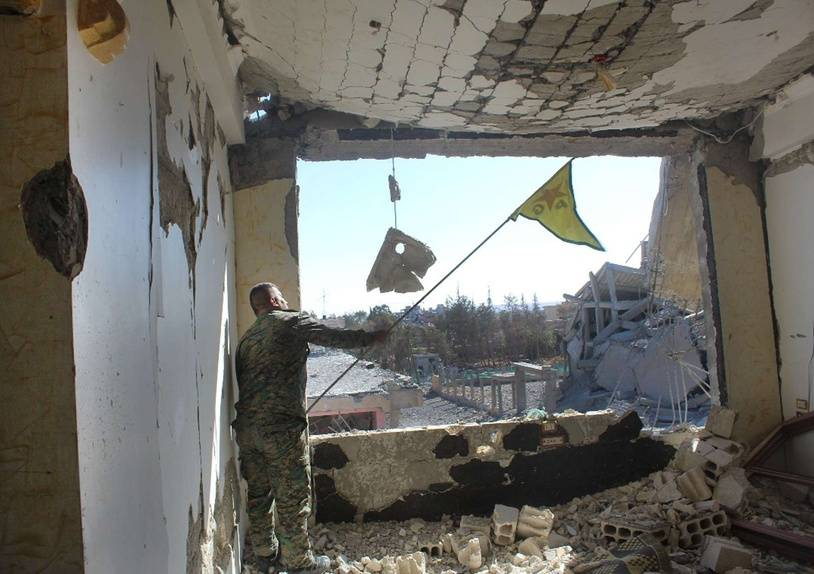 In this picture taken on Monday Oct. 16, 2017 and provided by The Syrian Democratic Forces (SDF), a U.S.-backed Syrian Kurdish forces outlet that is consistent with independent AP reporting, shows a Syrian Democratic Forces (SDF) fighter, waves his Kurdish party flag at the front line where they battle against the Islamic State militants, in Raqqa, Syria. The U.S-backed Syrian forces battling the Islamic State group in Syria say Raqqa's national hospital, one of the militants' last holdouts in city has been captured. AP PROVIDES ACCESS TO THIS THIRD PARTY PHOTO SOLELY TO ILLUSTRATE NEWS REPORTING OR COMMENTARY ON FACTS DEPICTED IN IMAGE; MUST BE USED WITHIN 14 DAYS FROM TRANSMISSION; NO ARCHIVING; NO LICENSING; MANDATORY CREDIT/1710171246
