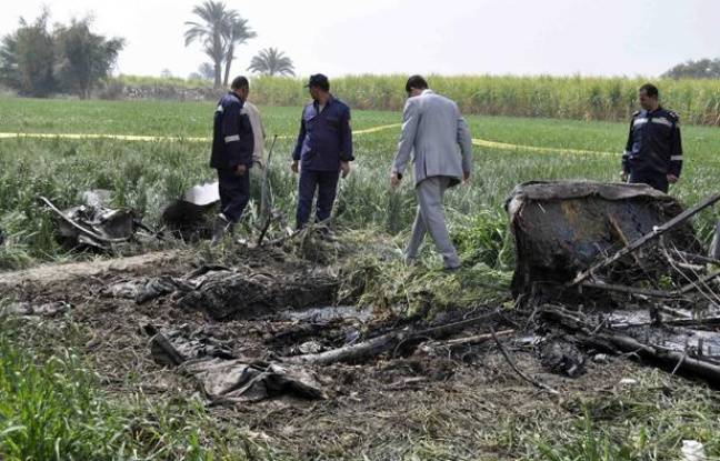 A rescue official examines a piece of wreckage from a hot air balloon that crashed in Luxor February 26, 2013. A hot air balloon crashed near the Egyptian town of Luxor at dawn on Tuesday after a mid-air gas explosion, killing 19 Asian and European tourists, a local industry official and the state news agency said.