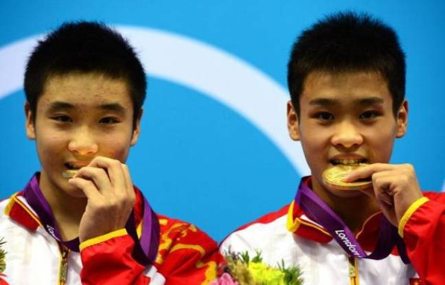 China's gold medalists Cao Yuan and Zhang Yanquan pose on the podium after the men's synchronised 10m platform final diving event at the London 2012 Olympic Games at the Olympic Park in London on July 30, 2012. AFP PHOTO / CHRISTOPHE SIMON