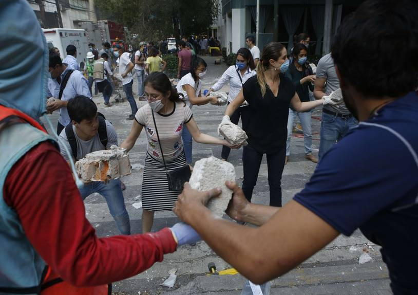 Volunteers pick up the rubble from a building that collapsed during an earthquake in the Condesa neighborhood of Mexico City, Tuesday, Sept. 19, 2017. A powerful earthquake jolted central Mexico on Tuesday, causing buildings to sway sickeningly in the capital on the anniversary of a 1985 quake that did major damage. (AP Photo/Rebecca Blackwell)/XLAT115/17262848326843/1709200148