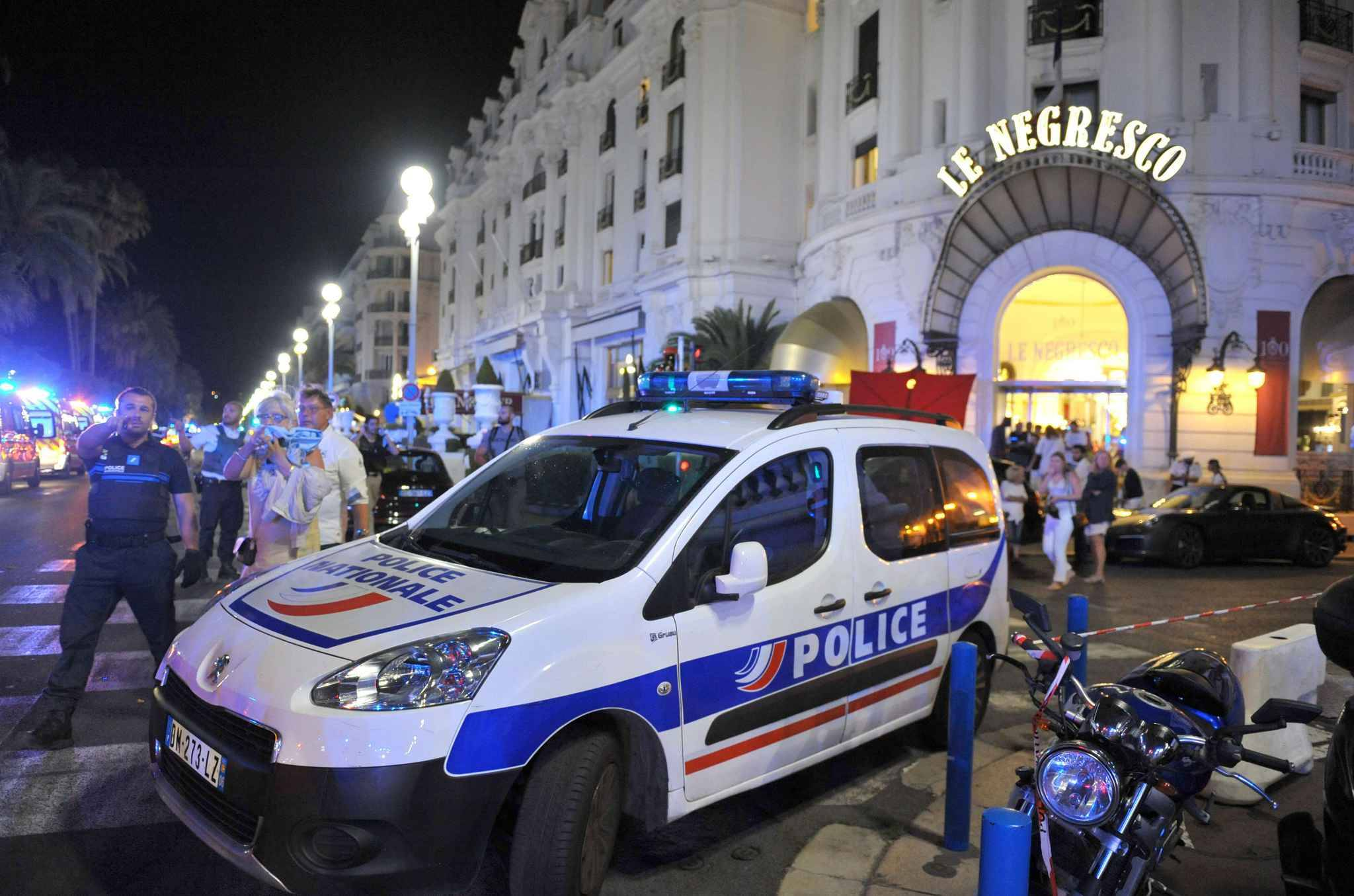 """A Police car is parked near the scene of an attack after a truck drove on to the sidewalk and plowed through a crowd of revelers who'd gathered to watch the fireworks in the French resort city of Nice, southern France, Friday, July 15, 2016. A spokesman for France's Interior Ministry says there are likely to be """"several dozen dead"""" after a truck drove into a crowd of revelers celebrating Bastille Day in the French city of Nice. (AP Photo/Christian Alminana)/REB106/335535924725/1607150256"""