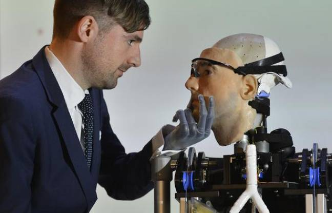 Swiss social psychologist Bertolt Mayer views 'Rex', a two metre tall artificial human, at the Science Museum in central London February 5, 2013. Mayer, a who uses a prosthetic hand himself, was used as the model for the 'bionic man', whom the British roboticist designers claim is the world's first complete bionic man, featuring artificial organs as well as fully functioning limbs. It will be on public display until March 11.
