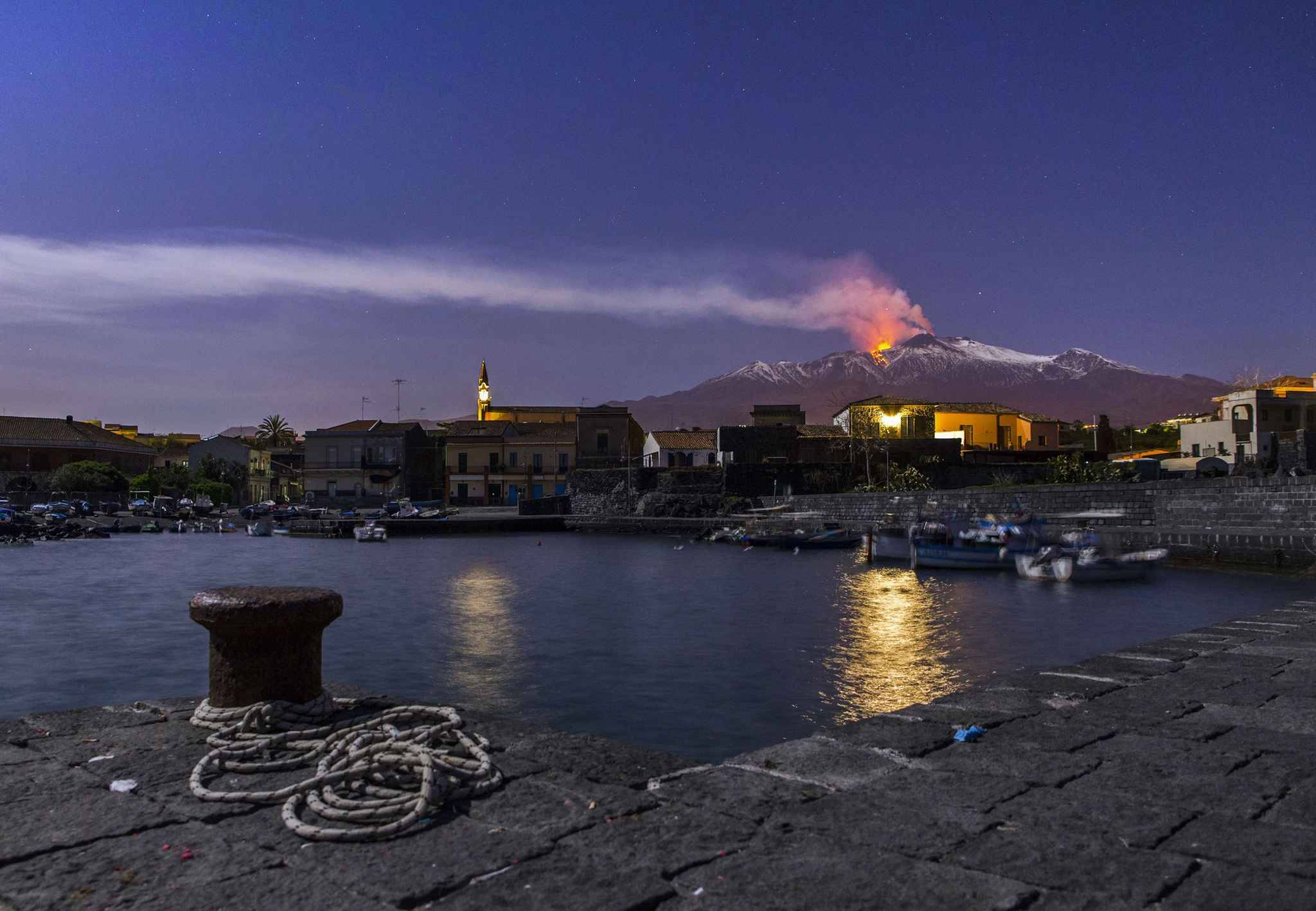 Snow-covered Mount Etna, Europe's most active volcano, spews lava during an eruption as the Sicilian village of Pozzillo, Italy, is visible in foreground, in the early hours of Tuesday, April 11, 2017.