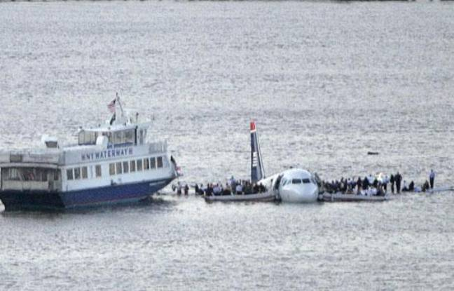 Passengers stand on the wings of a U.S. Airways plane as a ferry pulls up to it after it landed in the Hudson River in New York January 15, 2009.  A small plane carrying more than a dozen people splashed down in the frigid waters of the Hudson River off Manhattan on Thursday and survivors were seen standing on the wings awaiting rescue, Reuters witnesses said. REUTERS/Gary Hershorn (UNITED STATES)