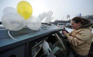 Des centaines de Moscovites ont roulé dimanche dans leurs voitures ornées de ballons et de rubans blancs autour du Kremlin pour protester contre le retour attendu du Premier ministre Vladimir Poutine au Kremlin après la présidentielle du 4 mars.