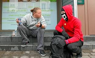 Masqué et vêtu d'un sweat à capuche rouge, Avalon distribue à manger et à boire aux sans-abri de Valenciennes.