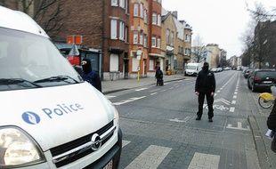 Des policiers belges bloquent l'accès où se déroule l'assaut dans le quartier de Molenbeek à Bruxelles, en Belgique le 18 mars 2016.