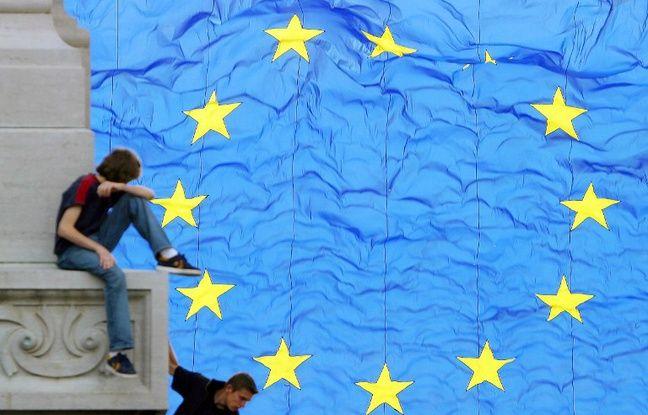 Des enfants jouent devant un drapeau européen, en mai 2004, à Bruxelles.