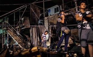 Des migrants devant des containers incendiés au camp de Moria, sur l'île de Lesbos, le 29 septembre 2019.