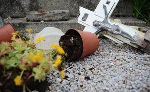 Crucifix et pot de fleurs renversés sur une tombe dégradée le 15 avril 2015 dans le cimetière à Castres