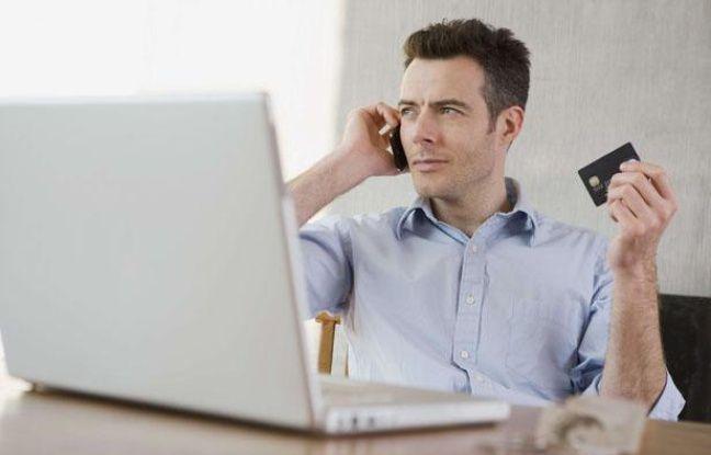 Un homme tient une carte de crédit et consulte son ordinateur portable