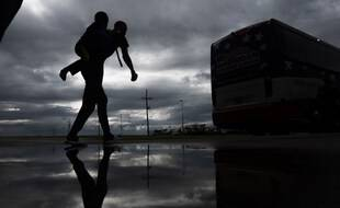 Un homme porte un garçon sur son dos, alors porte un enfant sur le dos alors qu'il se dirige vers un bus pour l'évacuation avant l'arrivée de l'ouragan Laura à Lake Charles, en Louisiane, le 25 août 2020 au milieu de la pandémie de coronavirus.