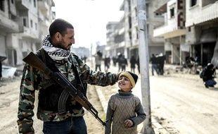 Un combattant kurde et son fils dans Kobané libérée, le 28 janvier 2015 (AFP / Bulent Kilic)