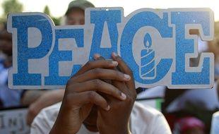 Une jeune fille recroquevillée devant un panneau «Paix» lors du rassemblement contre les armes, à Chicago, le 15 juin 2018.