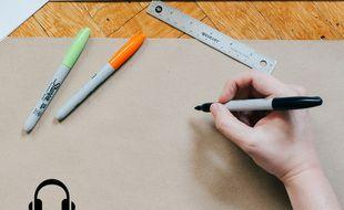 Illustration d'une personne face à une feuille de dessin, avec des marqueurs et une règle