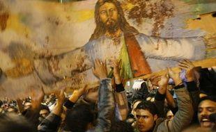 Des chrétiens d'Egypte brandissent un portrait de  Jesus Christ ensanglanté lors d'une manifestation, le 2 janvier 2011.