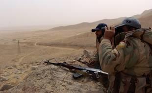 Deux soldats de l'armée syrienne observent les abords de Palmyre, jeudi 24 mars.