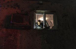 La police israélienne inspecte les dommages causés à une maison touchée par une roquette tirée depuis la bande de Gaza, dans un kibboutz près de la frontière, le 11mai 2021.