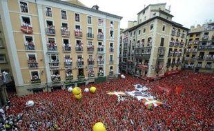 """Une marée humaine célèbre le """"chupinazo"""", le lancement rituel des festivités de la San Fermin devant la mairie de Pampelune, capitale de la Navarre, le 6 juillet 2014"""