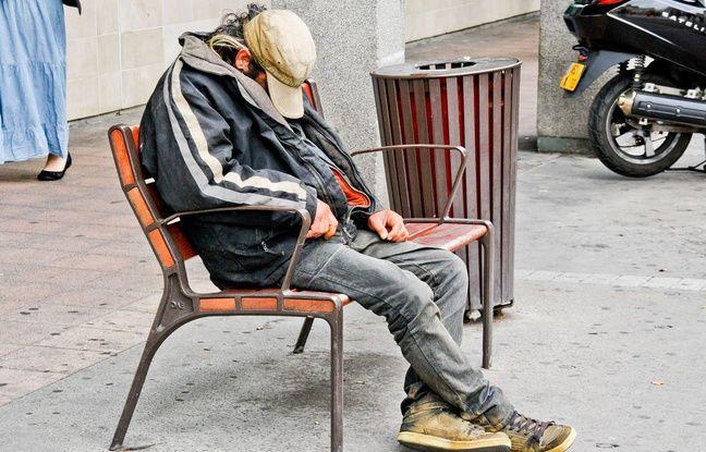 Un sans domicile fixe dort dans la rue.