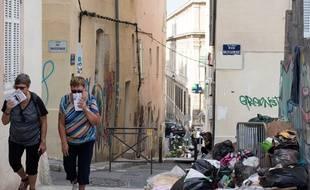 Des touristes marchent à côté de poubelle dans le quartier du Panier à Marseille