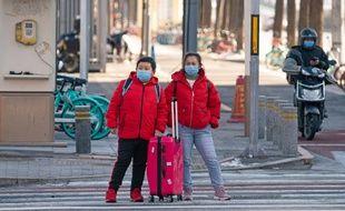 A Pékin, en Chine, des passants portent des masques pour se protéger, le 9 février 2020.