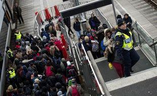 La police suédoise accompagne un groupe de migrants et réfugiés arrivant du Danemark, dans une gare près de Malmö, le 19 novembre 2015.
