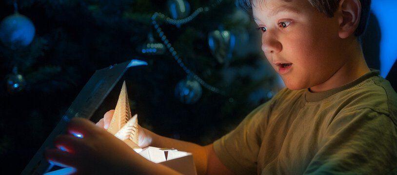 Un enfant découvre un cadeau de Noël