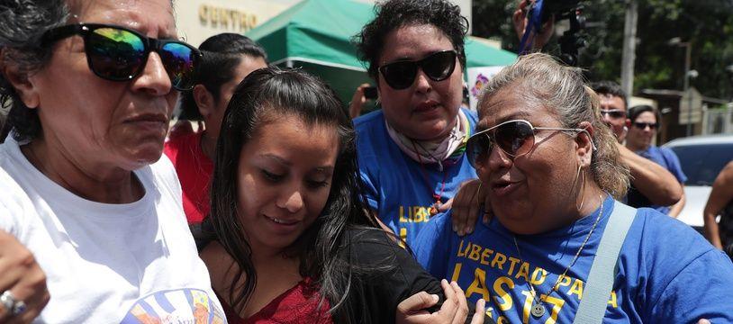 Evelyn Hernandez, en robe rouge, à la sortie du tribunal où le procureur a réclamé une peine de 40 ans de prison à son encontre, vendredi 16 août à San Salvador.