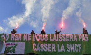 Des membres de SUD-Rail manifestent contre le projet de réforme de la SNCF, près de la gare de Lyon à Paris, le 12 mars 2018.