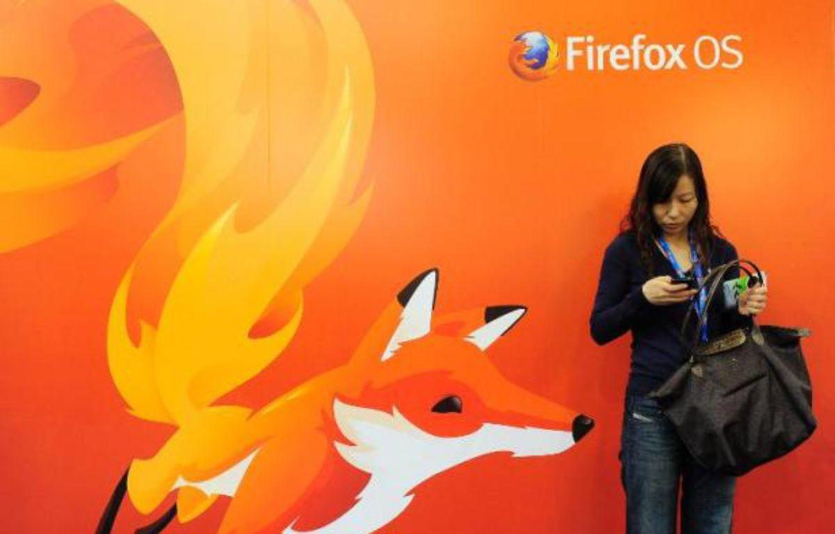 Une femme regarde son téléphone devant un poster de Mozilla Firefox à Barcelone au Congrès mondial de la téléphonie, le 27 février 2013 – Josep Lago AFP