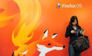 Une femme regarde son téléphone devant un poster de Mozilla Firefox à Barcelone au Congrès mondial de la téléphonie, le 27 février 2013