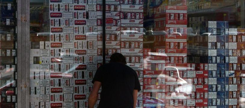 Un client devant un commerce de vente de cigarettes et d'alcool, au Pas-de-la-Case en Andorre.