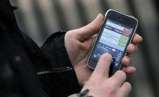 """Une personne utilise un iPhone le 18 décembre 2008 à Paris. Le groupe d'électronique grand public américain Apple s'est déclaré ce jour """"profondément déçu"""" de la décision du Conseil de la Concurrence de casser l'exclusivité dont bénéficie Orange (France Télécom) sur la vente de l'iPhone en France. Orange, qui commercialise l'iPhone depuis novembre 2007, bénéficiait d'une exclusivité de cinq ans, avec sortie anticipée possible au bout de trois ans. Le Conseil de la Concurrence a estimé la veille que """"l'exclusivité d'Orange sur l'iPhone (était) de nature à introduire un nouveau facteur de rigidité dans un secteur qui souffre déjà d'un déficit de concurrence"""". AFP PHOTO / STEPHANE DE SAKUTIN"""