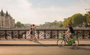 Le 23 juillet 2018, à Paris (4e). Un cycliste à Vélib circule dans une voie cyclable, sur le pont Notre-Dame.