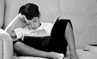 Un enfant lit un livre chez lui.