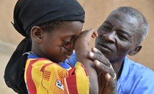 Un infirmier prodigue des soins à une petite fille souffrant du noma, une maladie causée par la malnutrition, le 26 mai 2015 dans un centre médical de l'ONG Sentinelles à Zinder, dans le sud du Niger