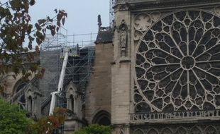 Les pompiers continuent d'arroser Notre-Dame de Paris au lendemain matin de l'incendie.