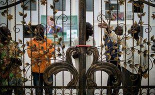 Des militants du parti d'opposition congolais UPADS derrière les grilles cadenassées du siège de leur parti à Brazzaville, le 25 mars 2016