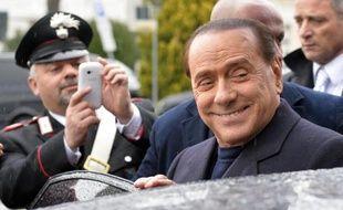 L'ex chef du gouvernement italien Silvio Berlusconi à son arrivée à l'aéroport Fiumicino près de Rome, le 25 mars 2014. Le justice se penche jeudi sur sa requête d'effectuer des travaux d'intérêt général après sa condamnation à un an de prison