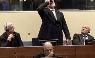 This videograb taken from live footage of the International Criminal Court, shows Croatian former general Slobodan Praljak swallowing what is believed to be poison, during his judgement at the UN war crimes court to protest the upholding of a 20-year jail term. Former Bosnian Croat military leader Slobodan Praljak was alive and being treated by medics. AFP