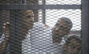 Le journaliste égypto-canadien Mohamed Fadel Fahmy (c) avec ses collègues Peter Greste (g) et Baher Mohamed, lors de son procès au Caire, le 23 juin 2014