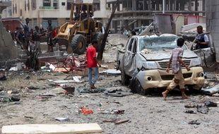 Des habitants d'Aden inspectent le lieu de l'attentat à la voiture piégée, le 29 août 2016.
