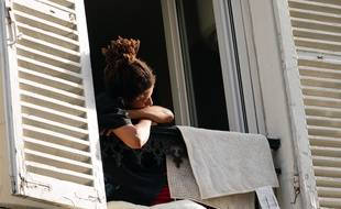 Une personne regarde par la fenêtre en période de confinement.