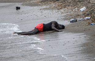 Un homme est allongé par terre sur la plage après avoir nagé du Maroc vers l'Espagne, dans l'enclave espagnole de Ceuta, le mardi 18 mai 2021.